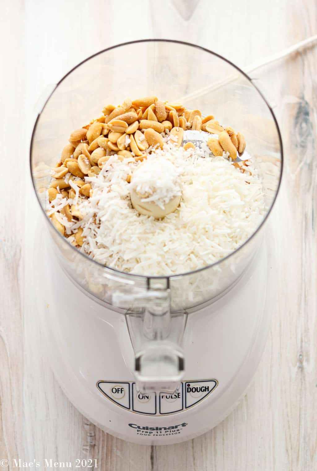 A food processor with peanuts and dried coconut