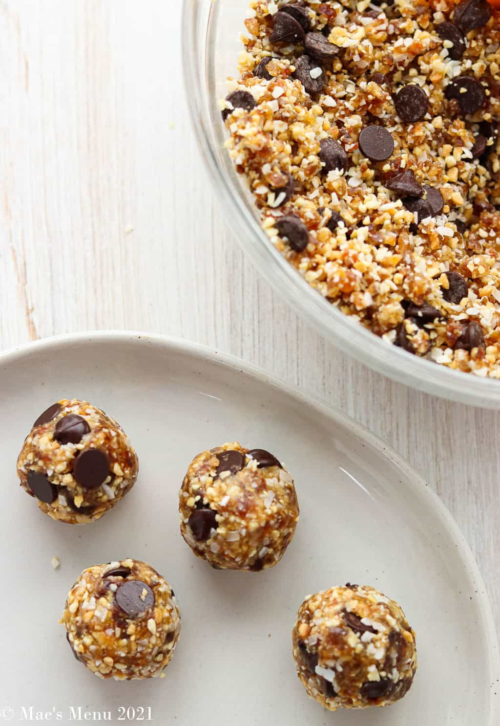 A few date balls rolled out on a plate next to the clear glass bowl of the date and coconut mixture