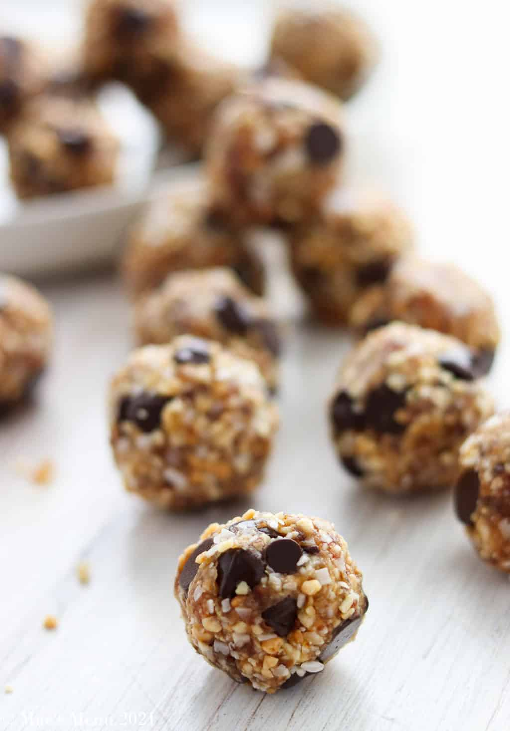 Date balls on a piece of wood in front of a plate of the balls