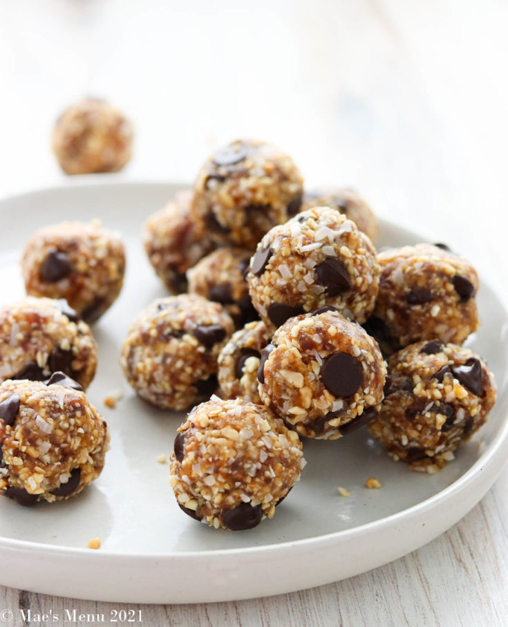 A side angled shot of a white plate of date energy balls