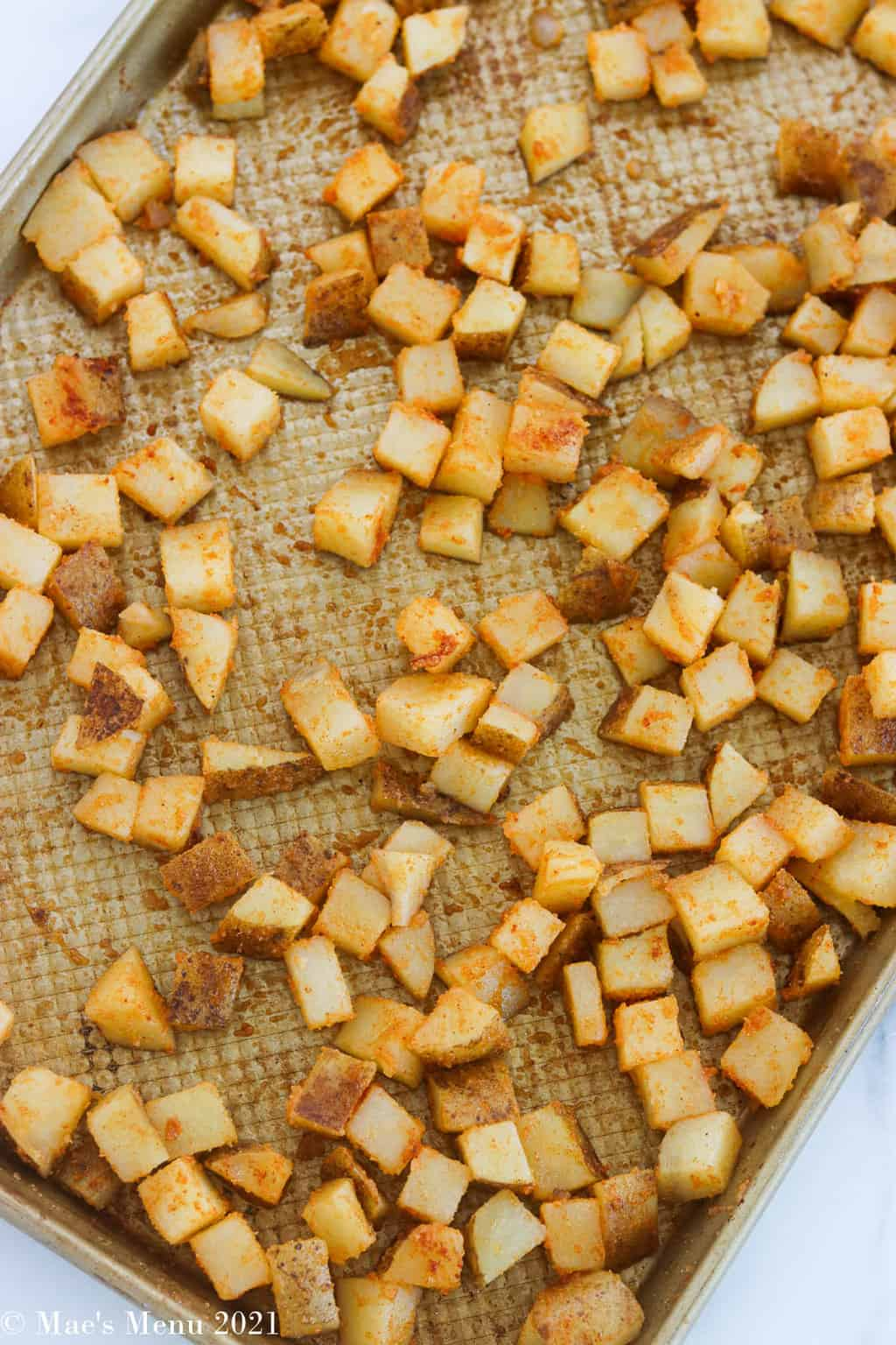 Potatoes tossed with the seasonings on a baking sheet