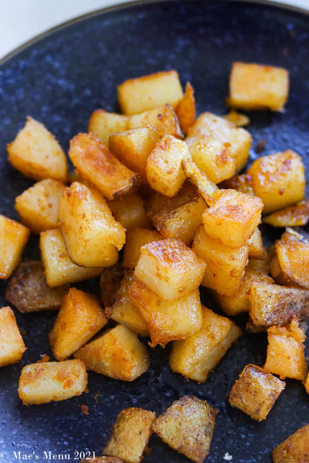an up-close shot of home fries on a blue plate