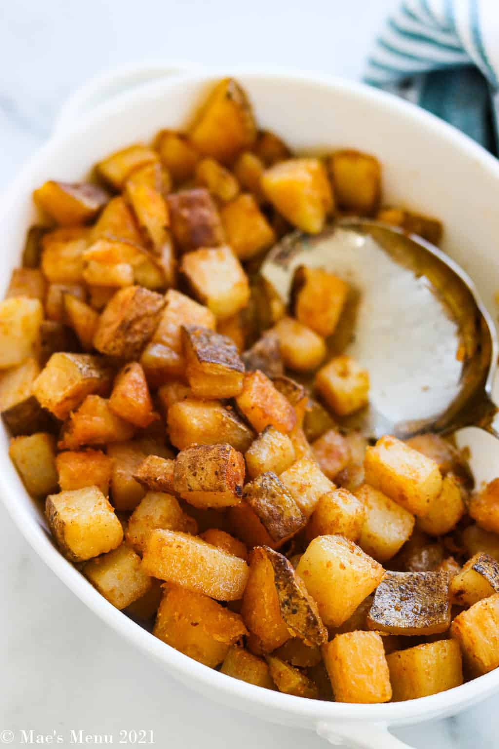 A dish of home fries with a large serving spoon in it