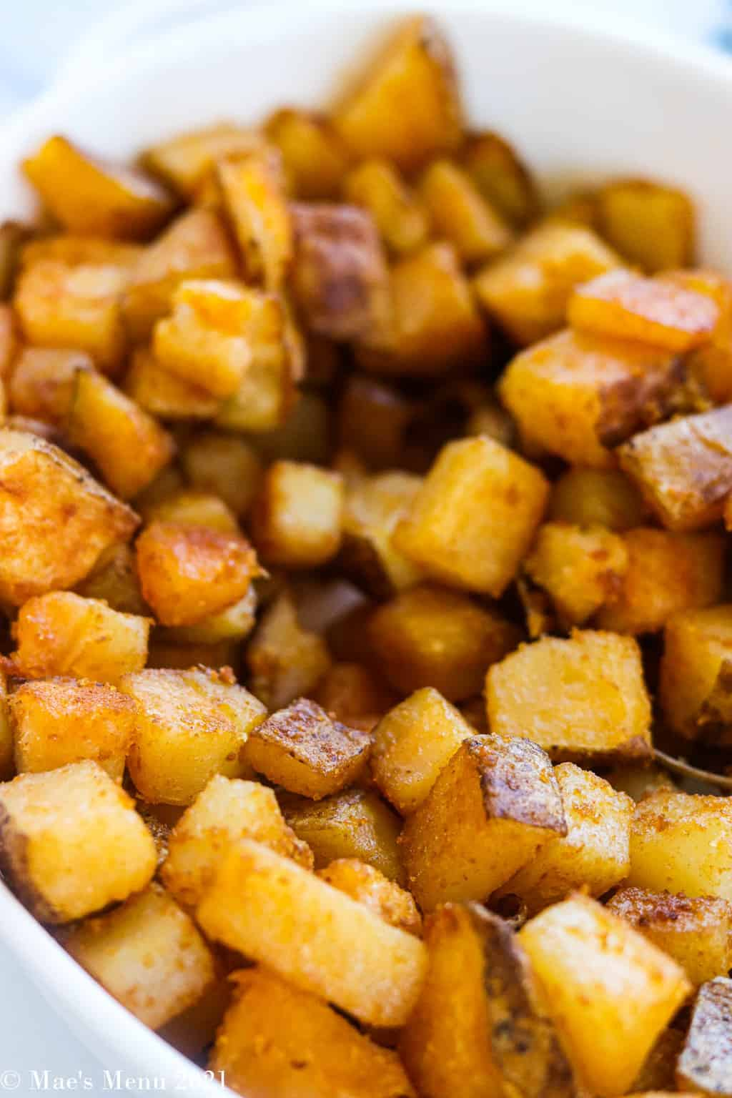 An up-close shot of home fries in a white bowl