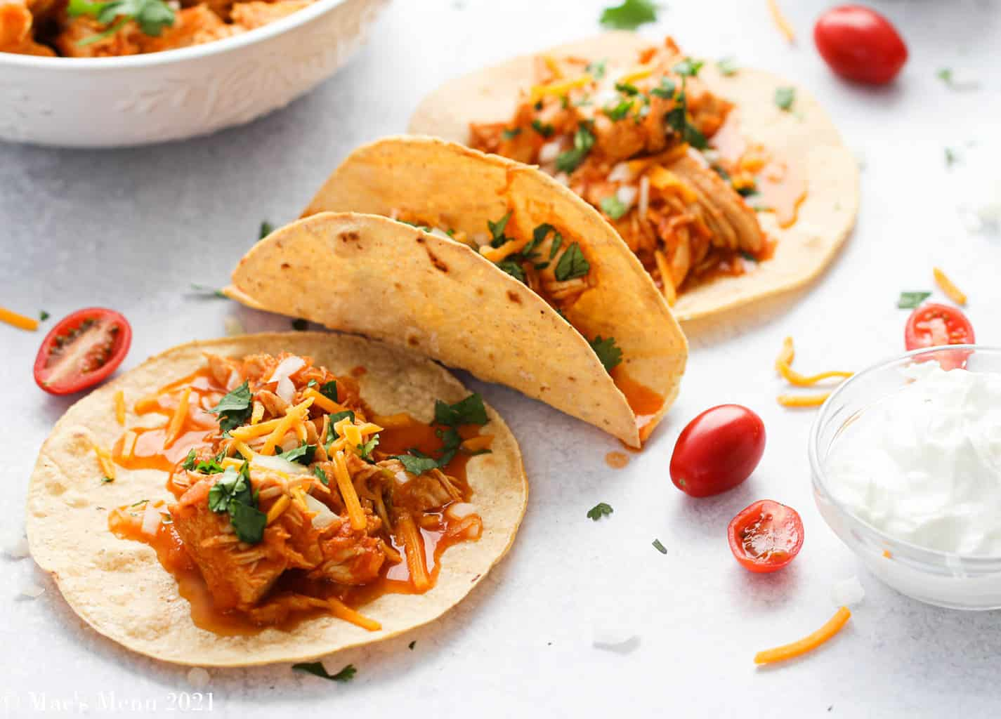 3 instant pot shredded chicken tacos on a counter