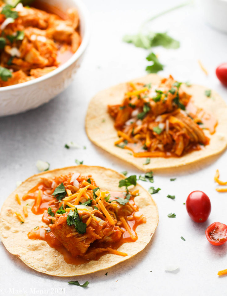 Two instant pot shredded chicken tacos on a counter