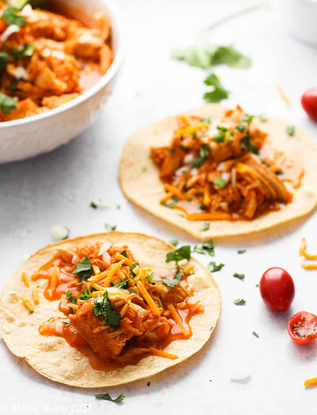 two instant pot chicken tacos on tortillas with tomatoes, cilantro, and onions