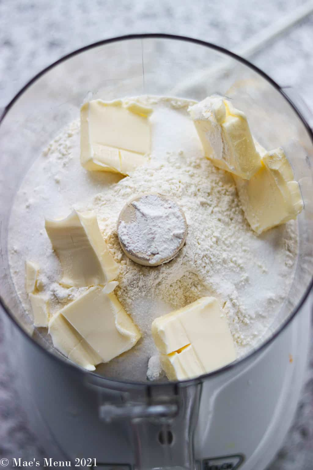 A food processor with flour, sugar, and butter cubes