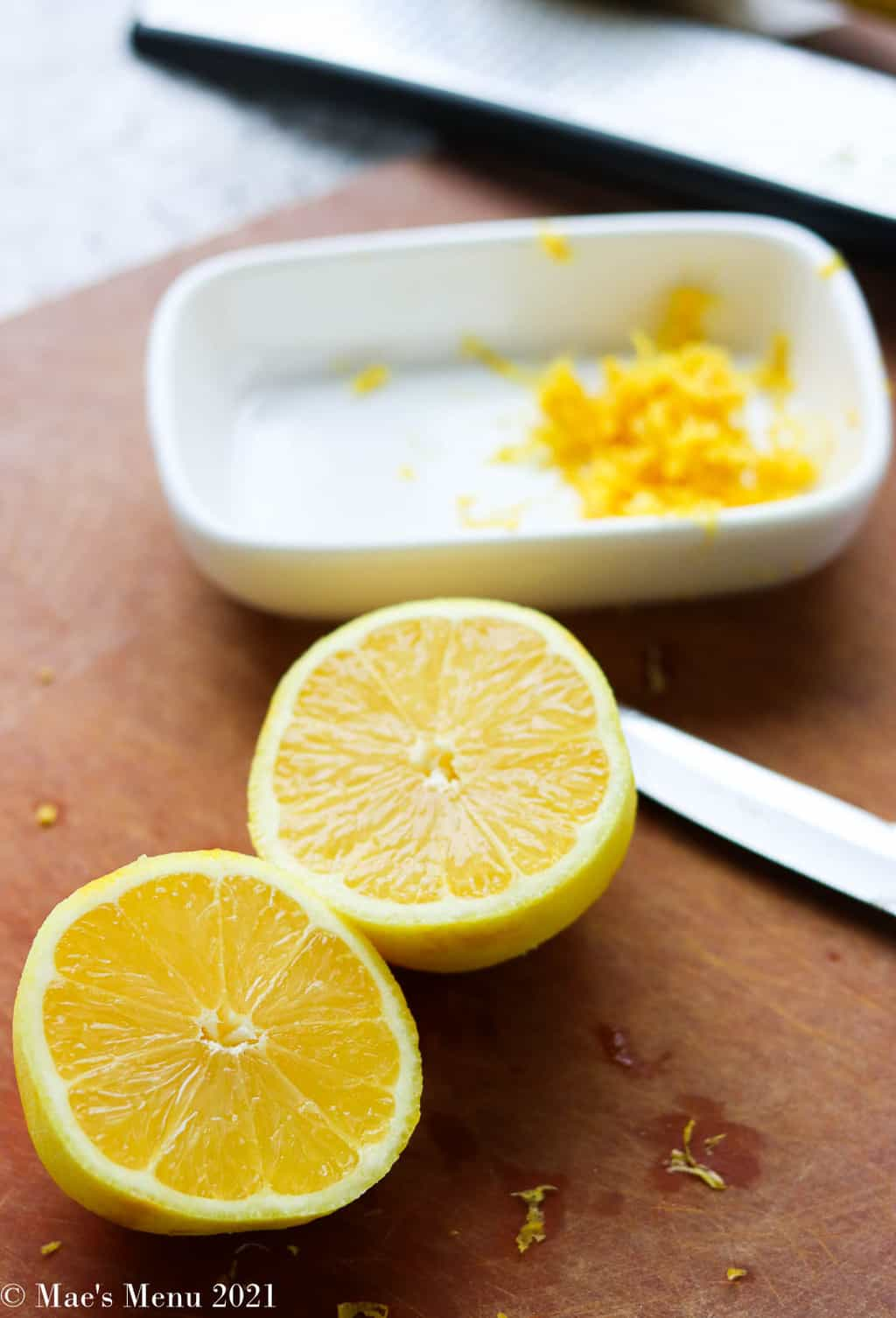 A lemon cut in half with a dish of lemon zest in the back