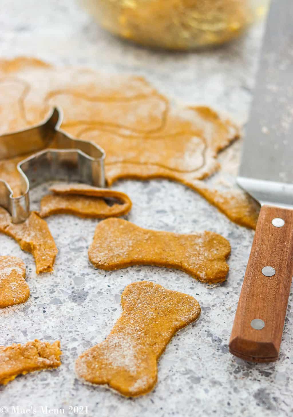 Cutting bone shape treats out of a rolled out piece of pumpkin peanut butter dough