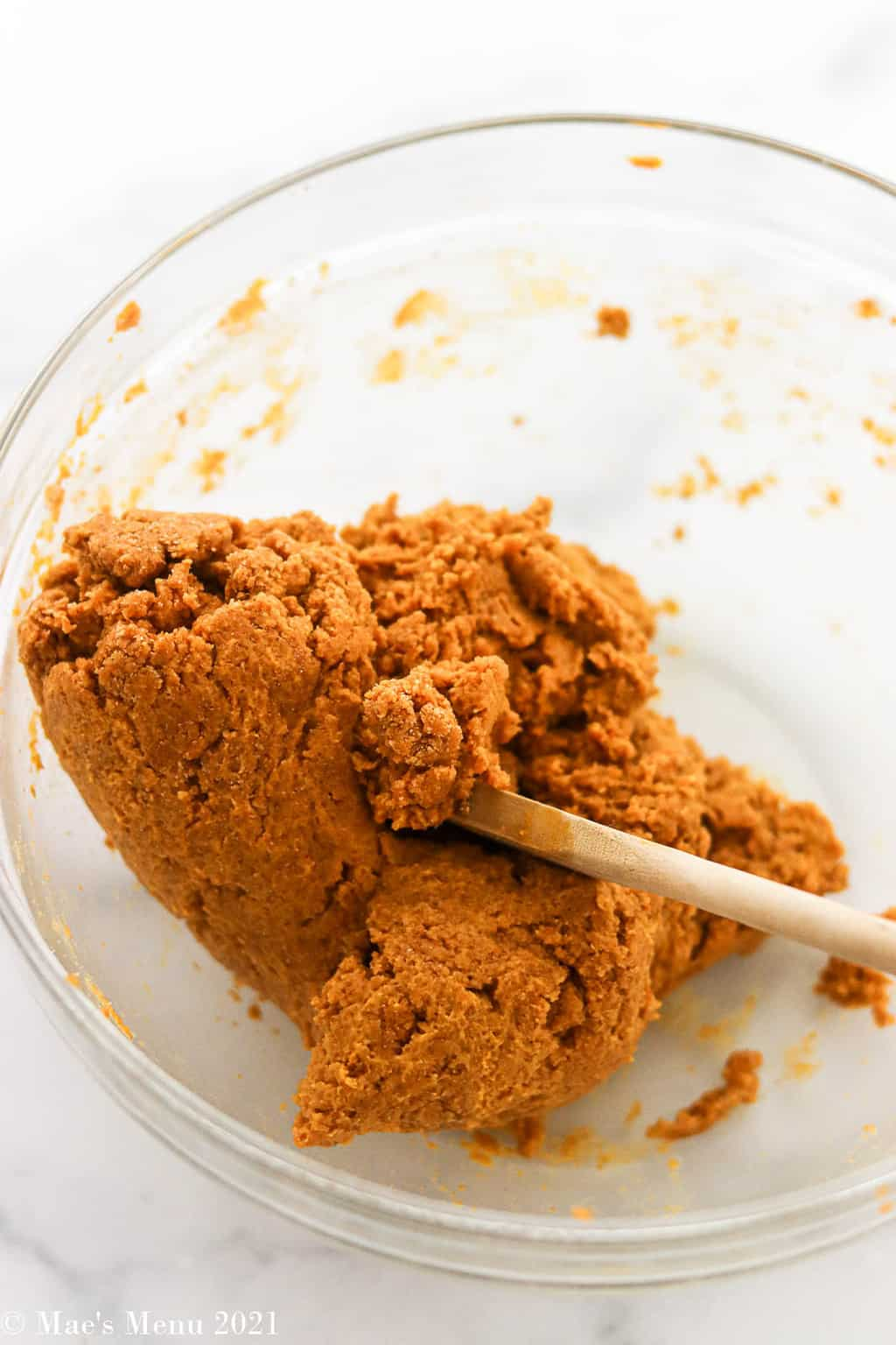 The peanut butter pumpkin dough in a mixing bowl with a wooden spoon