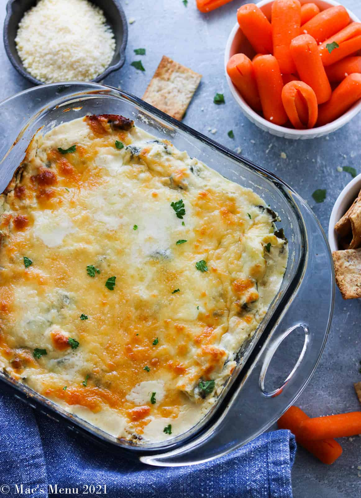 An overhead shot of a pan of spinach artichoke dip surrounded by cups of carrots, crackers, cheese, and more