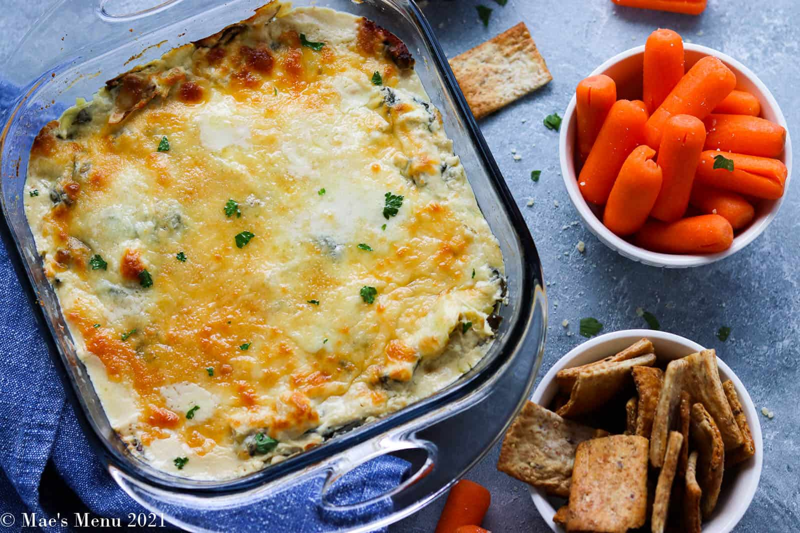 An overhead shot of a pan of spinach artichoke dip next to crackers and carrots