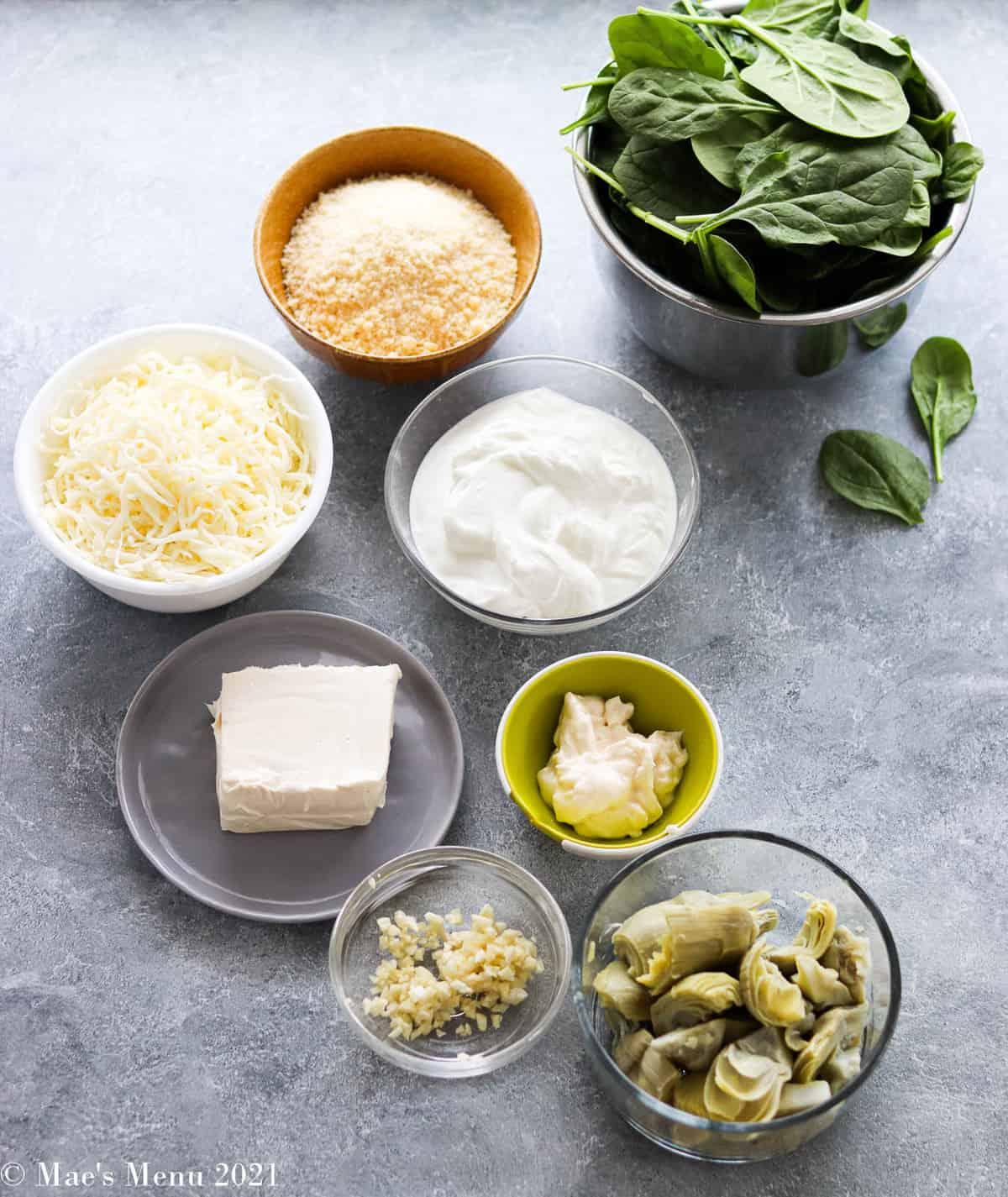 All the ingredients for spinach artichoke dip: mozzarella cheese, parmesan, Greek yogurt, baby spinach, light cream cheese, mayonnaise, artichoke hearts, and garlic