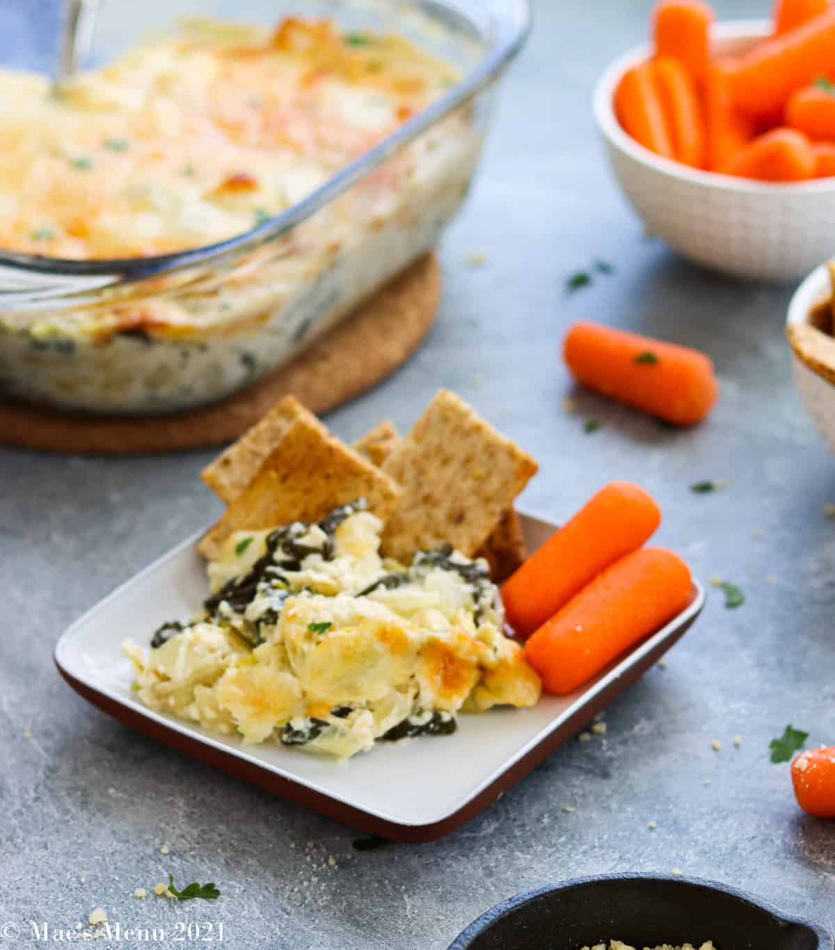 A dish of artichoke dip with crackers and carrots in front of a pan of the dip