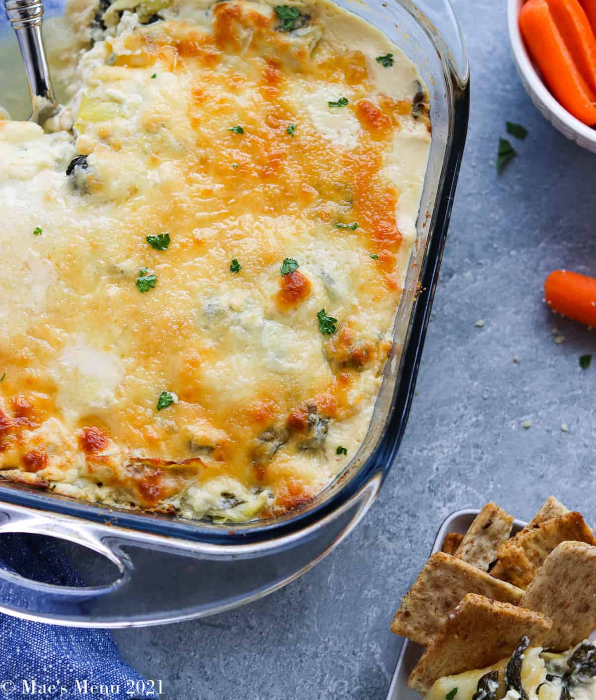 An overhead shot of a corner or spinach artichoke dip next to a small dish of the dip with crackers and a cup of carrots