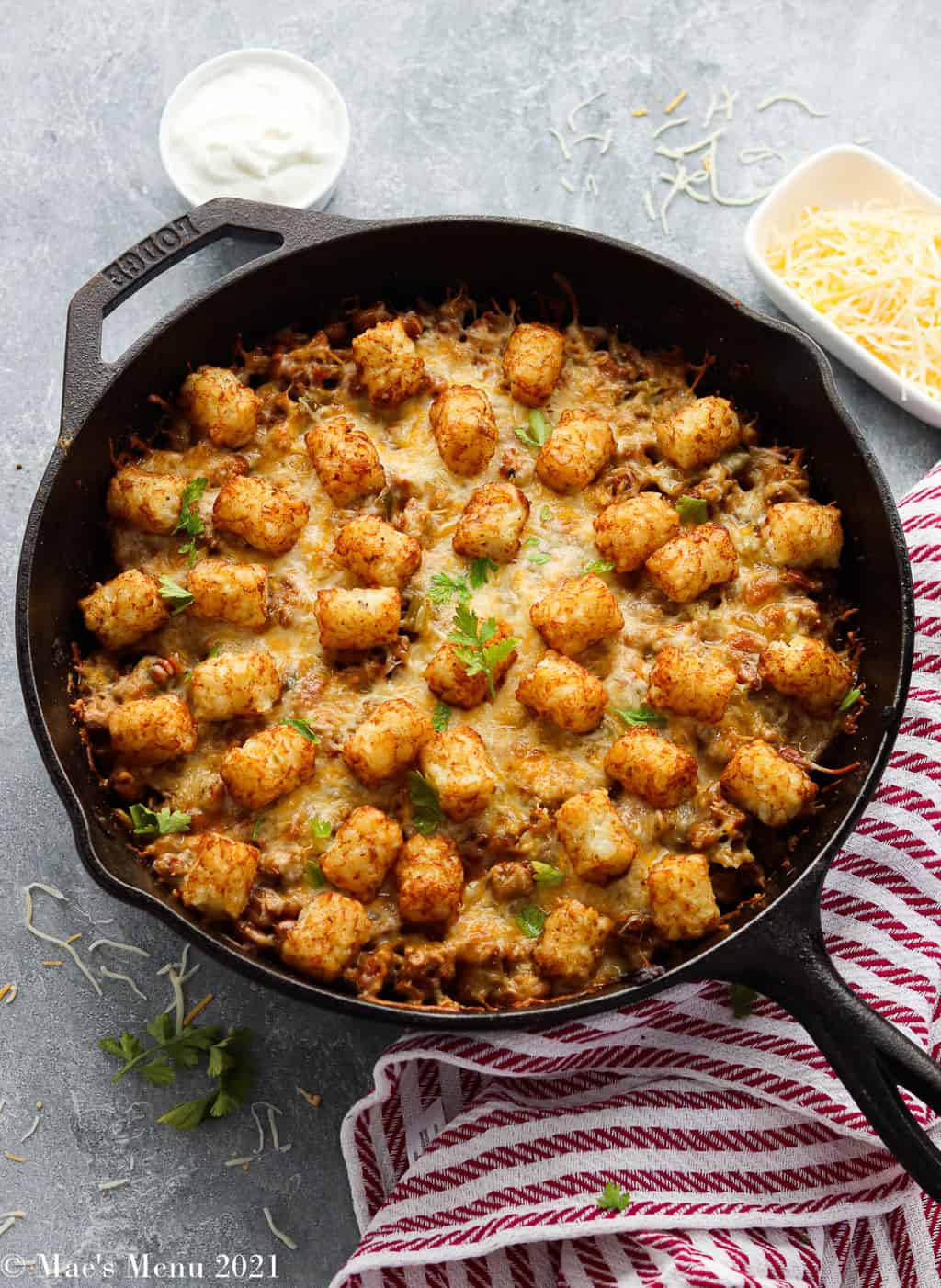 An overhead shot of a cast iron skillet of taco tater tot casserole