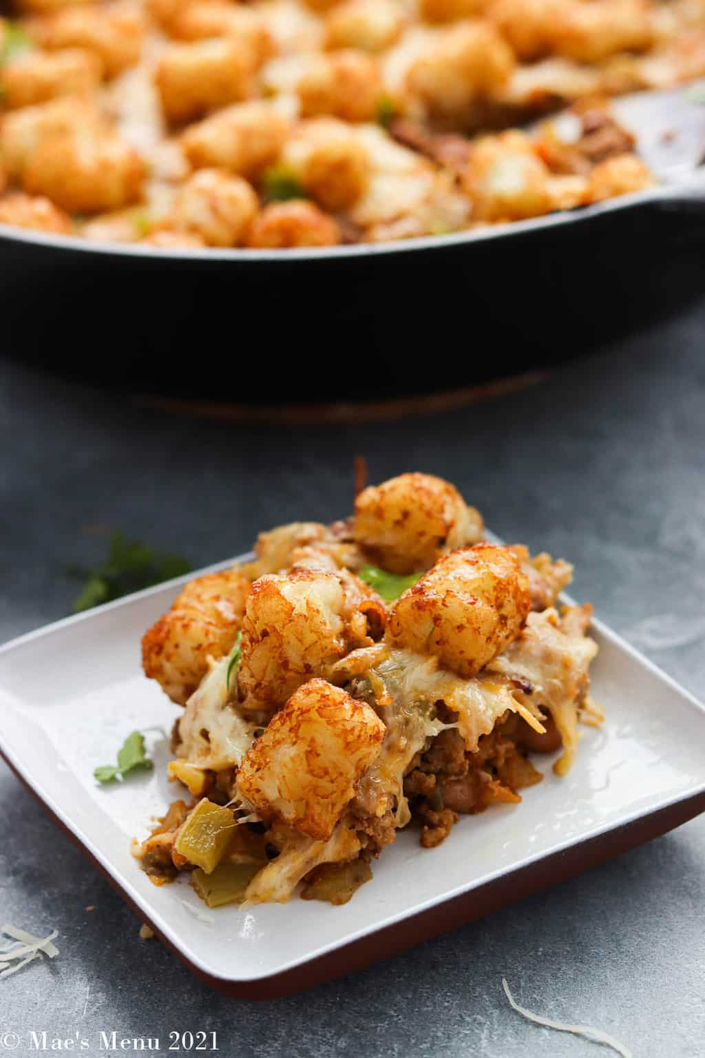 A small dish of taco tater tot casserole in a sheet in front of the cast iron skillet