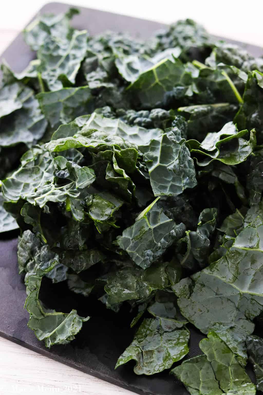 A cutting board full of chopped lacinato kale