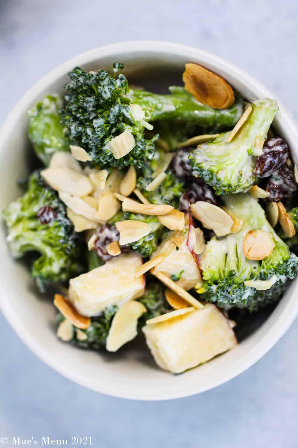 An up-close overhead shot of a bowl of broccoli raisin salad