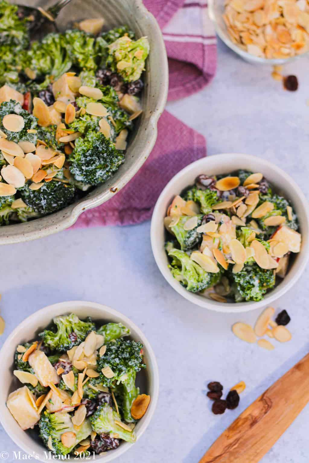 An overhead shot of 2 small bowl s of healthy broccoli raisin salad next to a large bowl of the rest of the salad