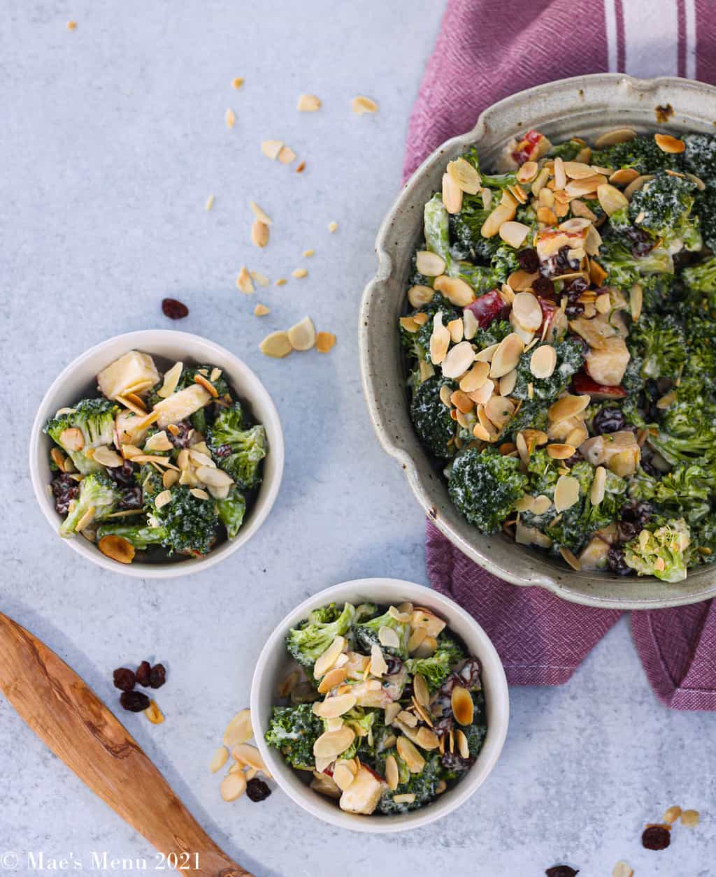 An up-close overhead shot of two small bowls of broccoli raisin salad next to a large bowl of the salad