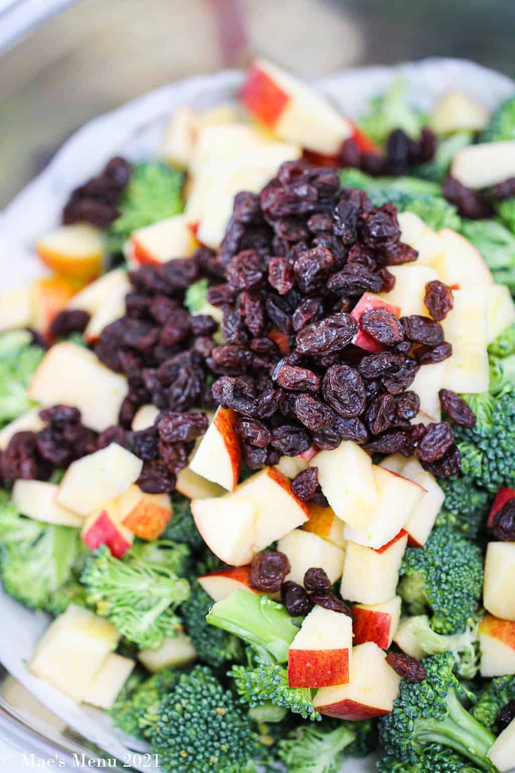 a large mixing bowl with all the ingredients for broccoli raisin salad