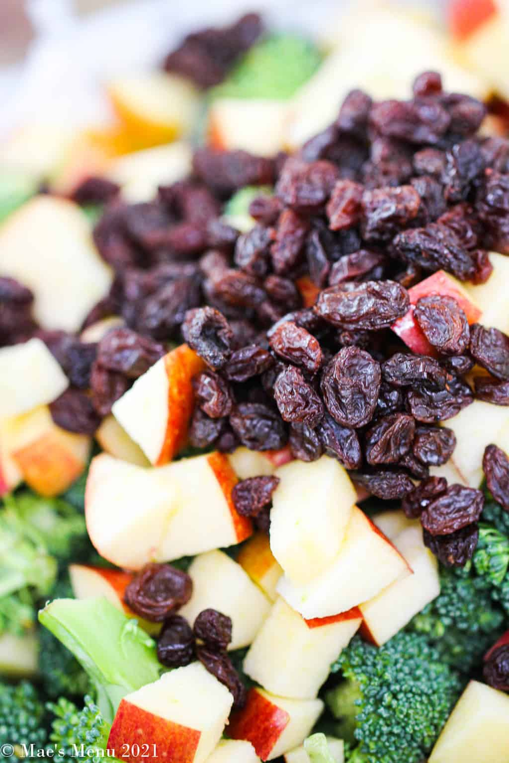 An up-close shot of raisins, applse, and broccoli in a large mixing bowl