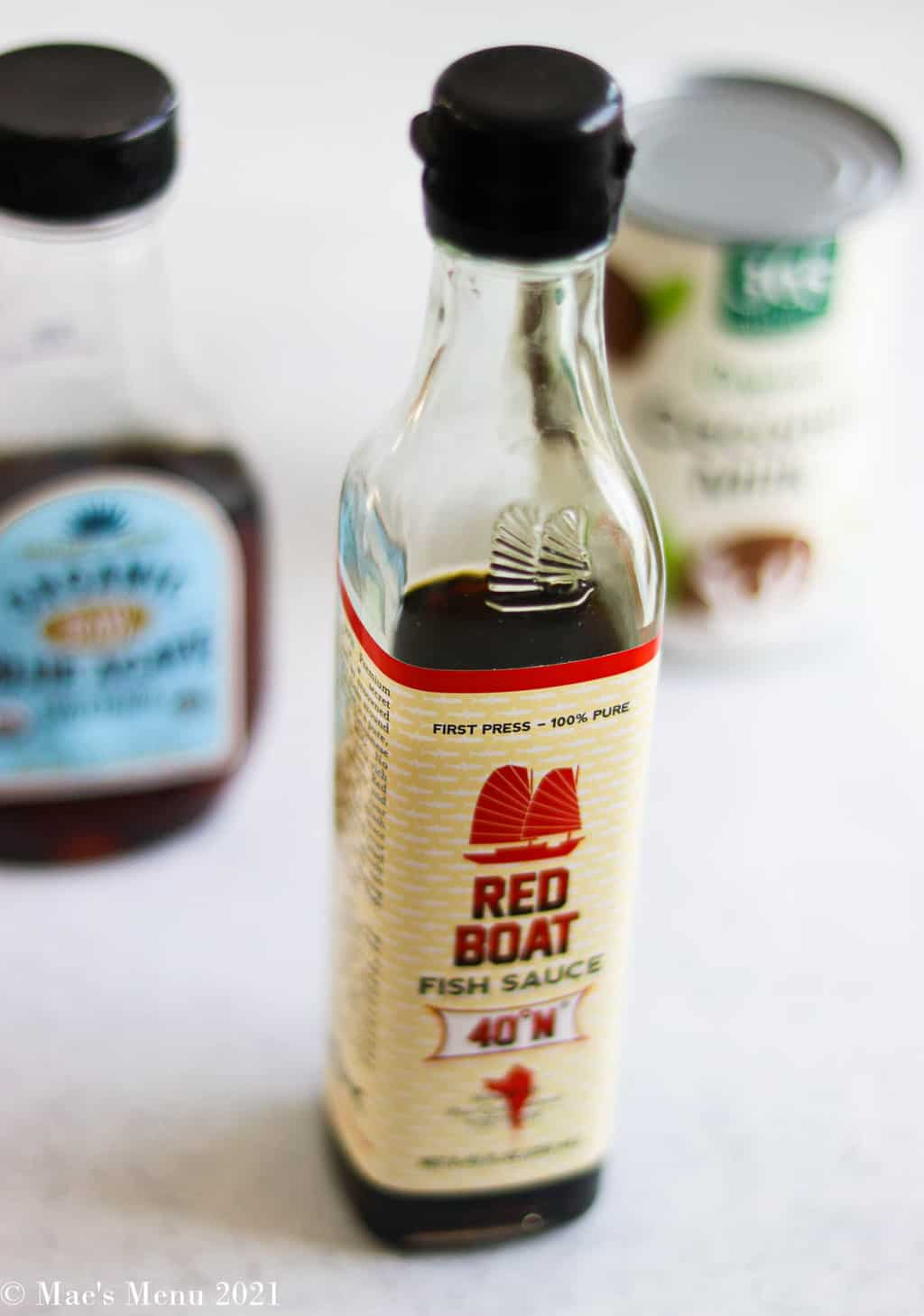 A bottle of red boat fish sauce sitting in front of agave syrup and coconut milk