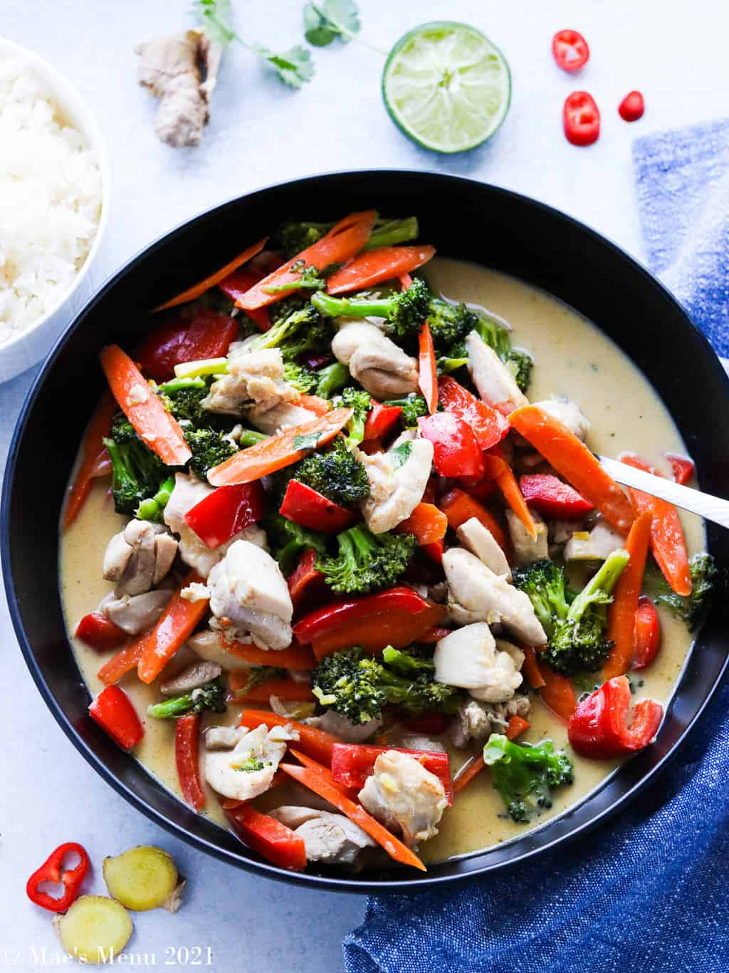 A vertical shot of a large black bowl of thai green chicken curry