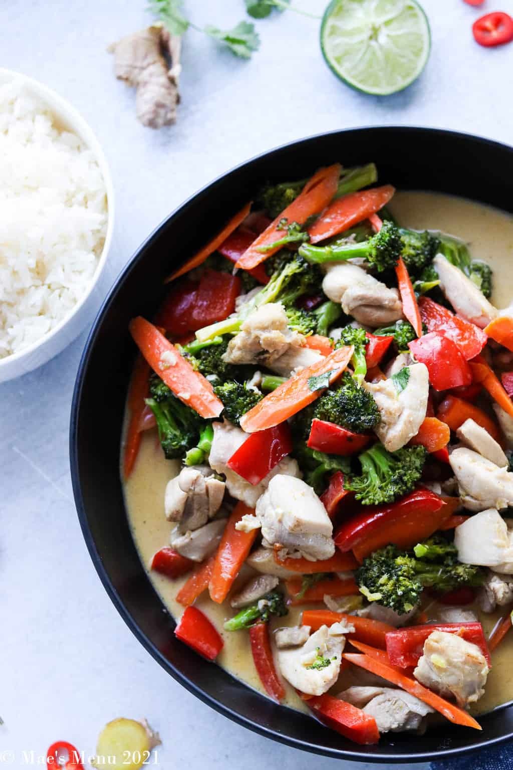A large black bowl of thai green chicken curry next to a small bowl of rice