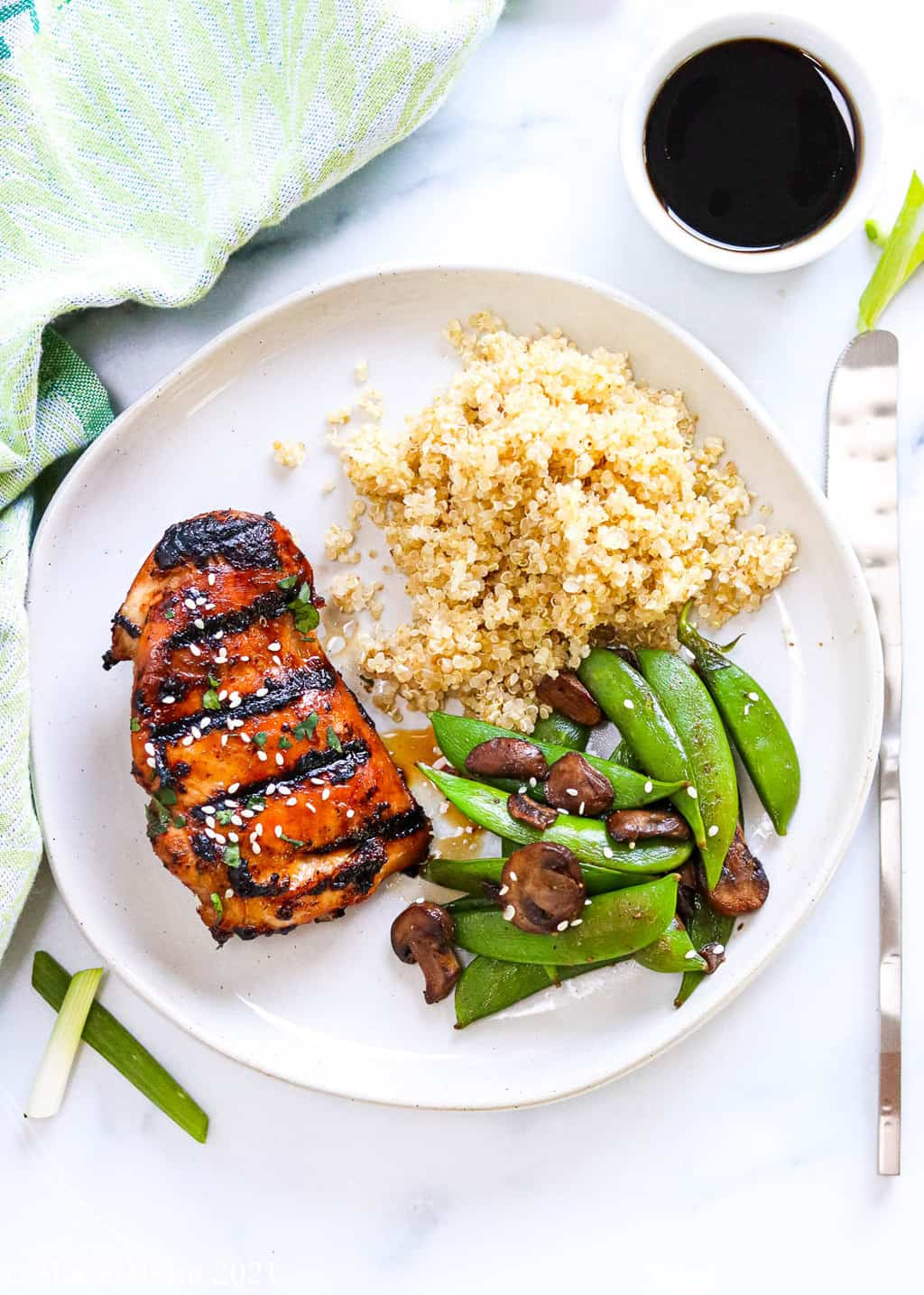 A plate of quinoa, veggies, and Asian marinated chicken