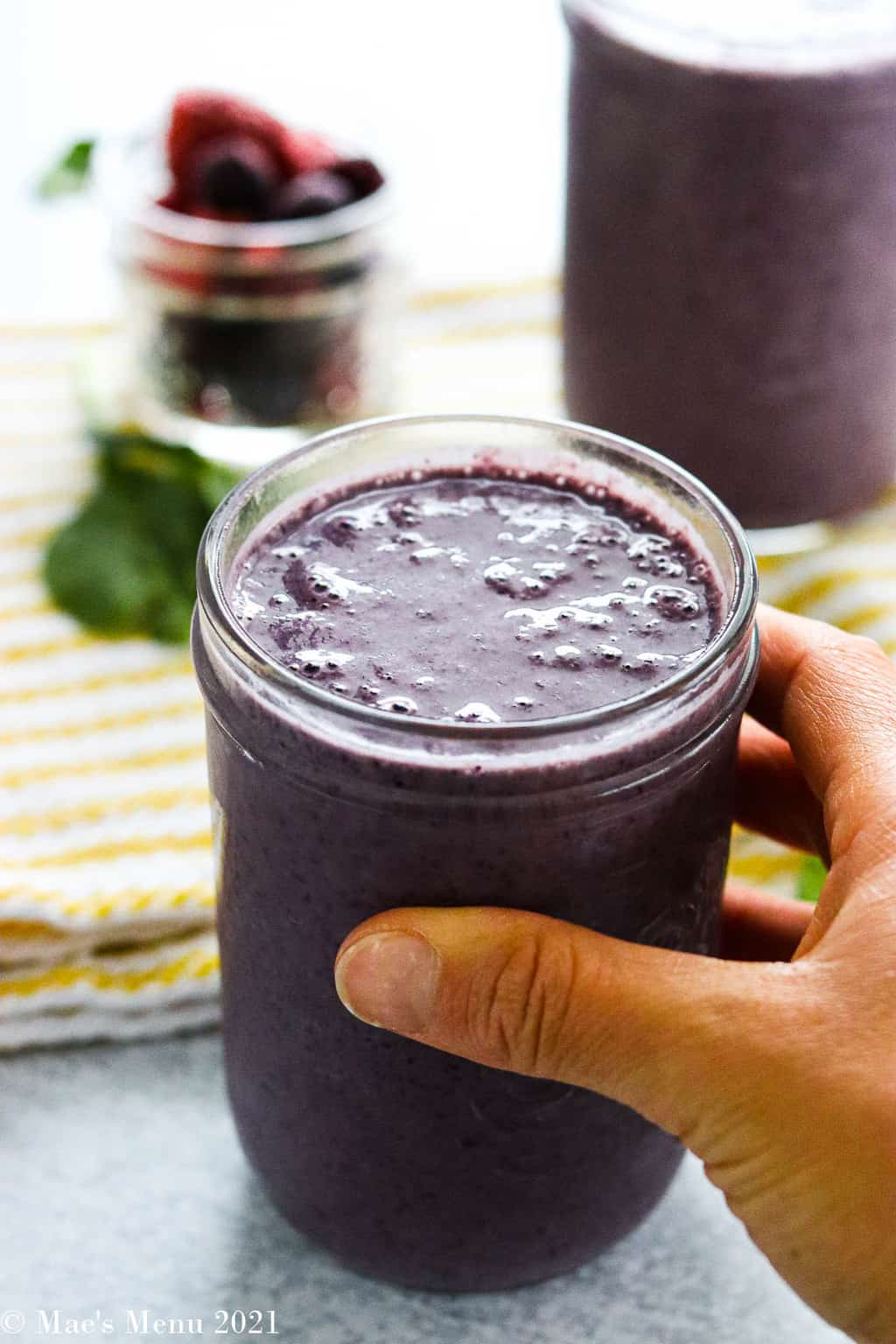 A hand holding a cup of blueberry spinach smoothie