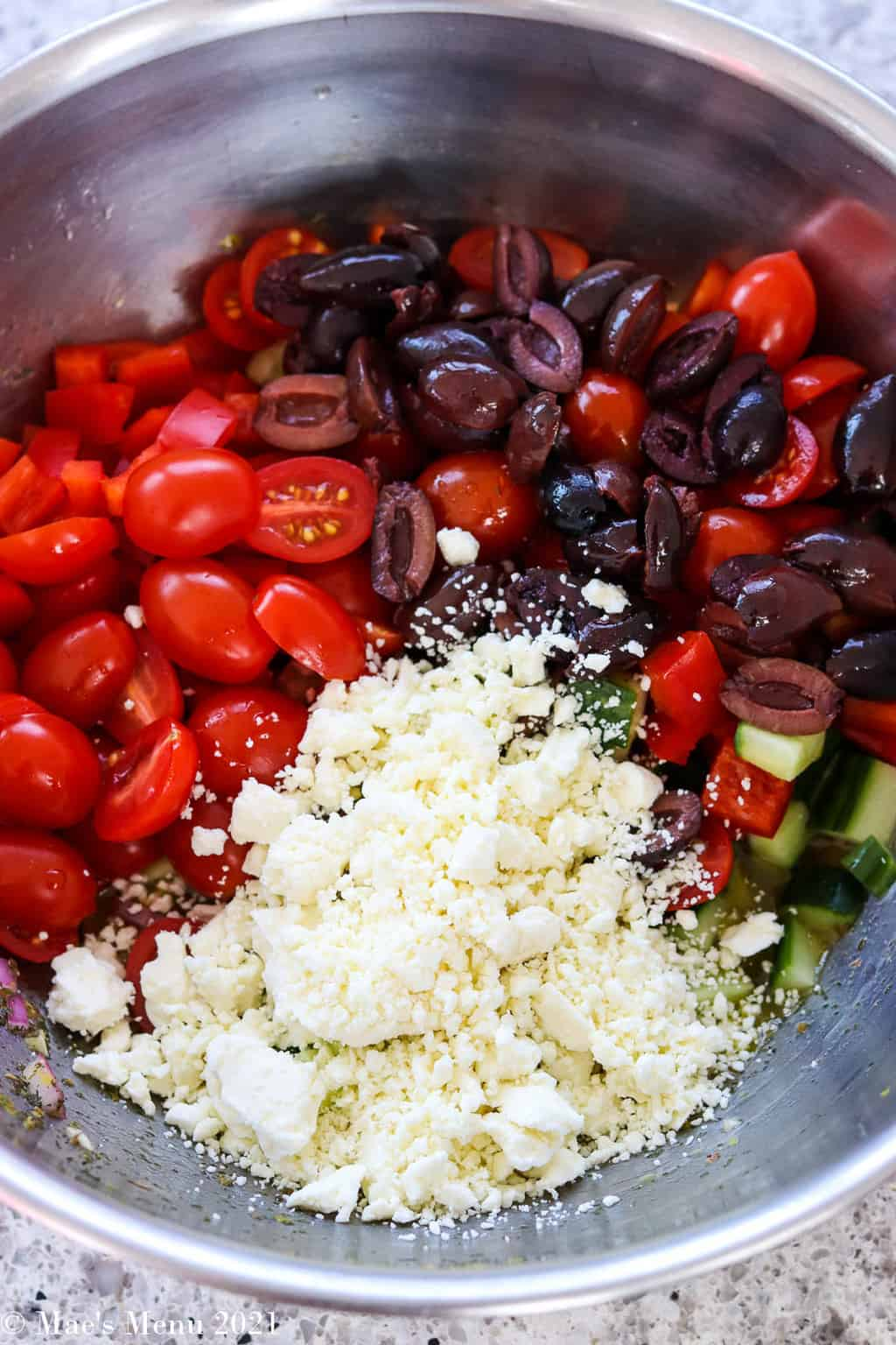A large mixing bowl with cherry tomatoes, olives, and feta cheese