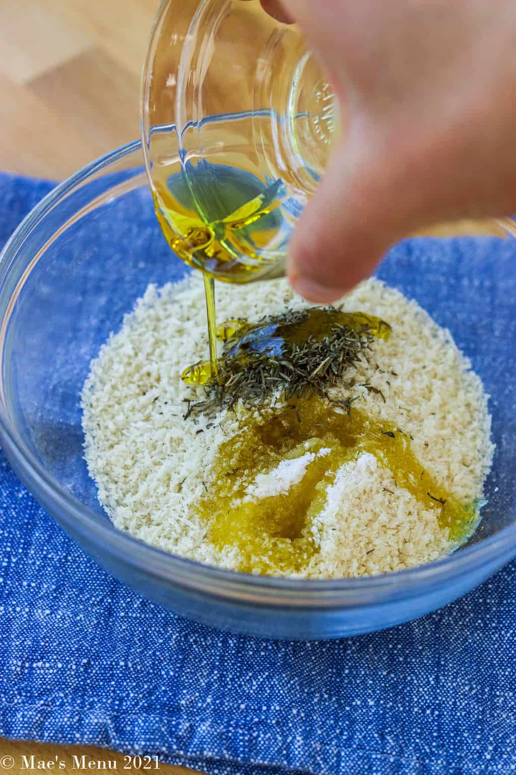 A small mixing bowl of panko, herbs, and salt with a hand pouring olive oil over