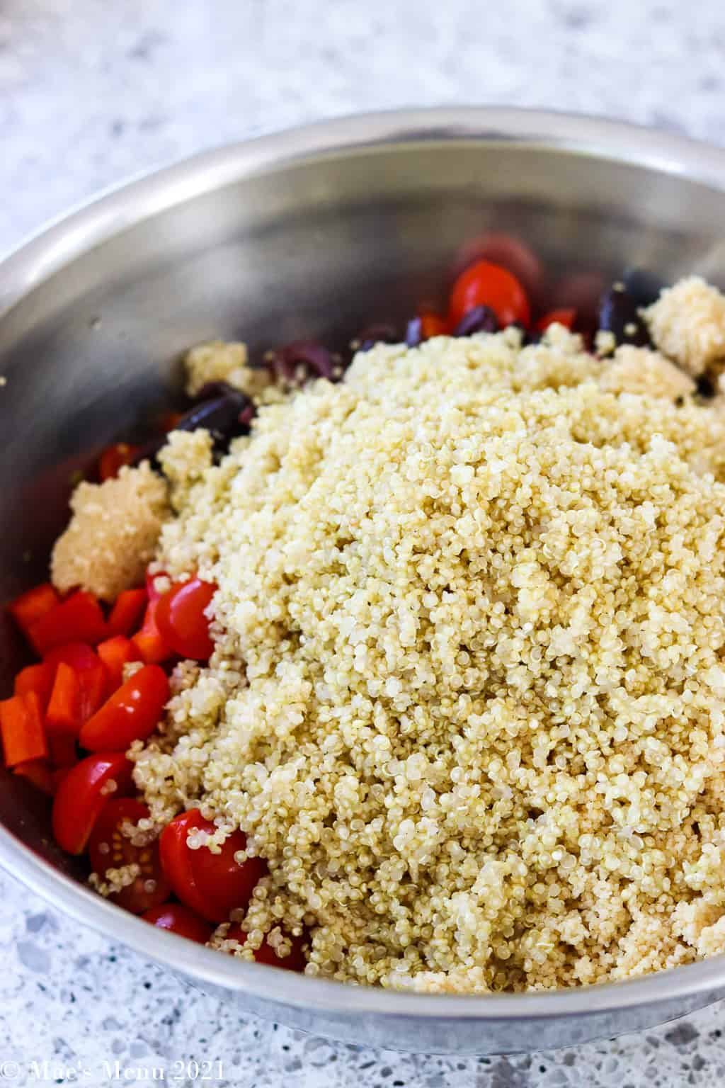 A large mixing bowl with veggies and a big pile of quinoa on top
