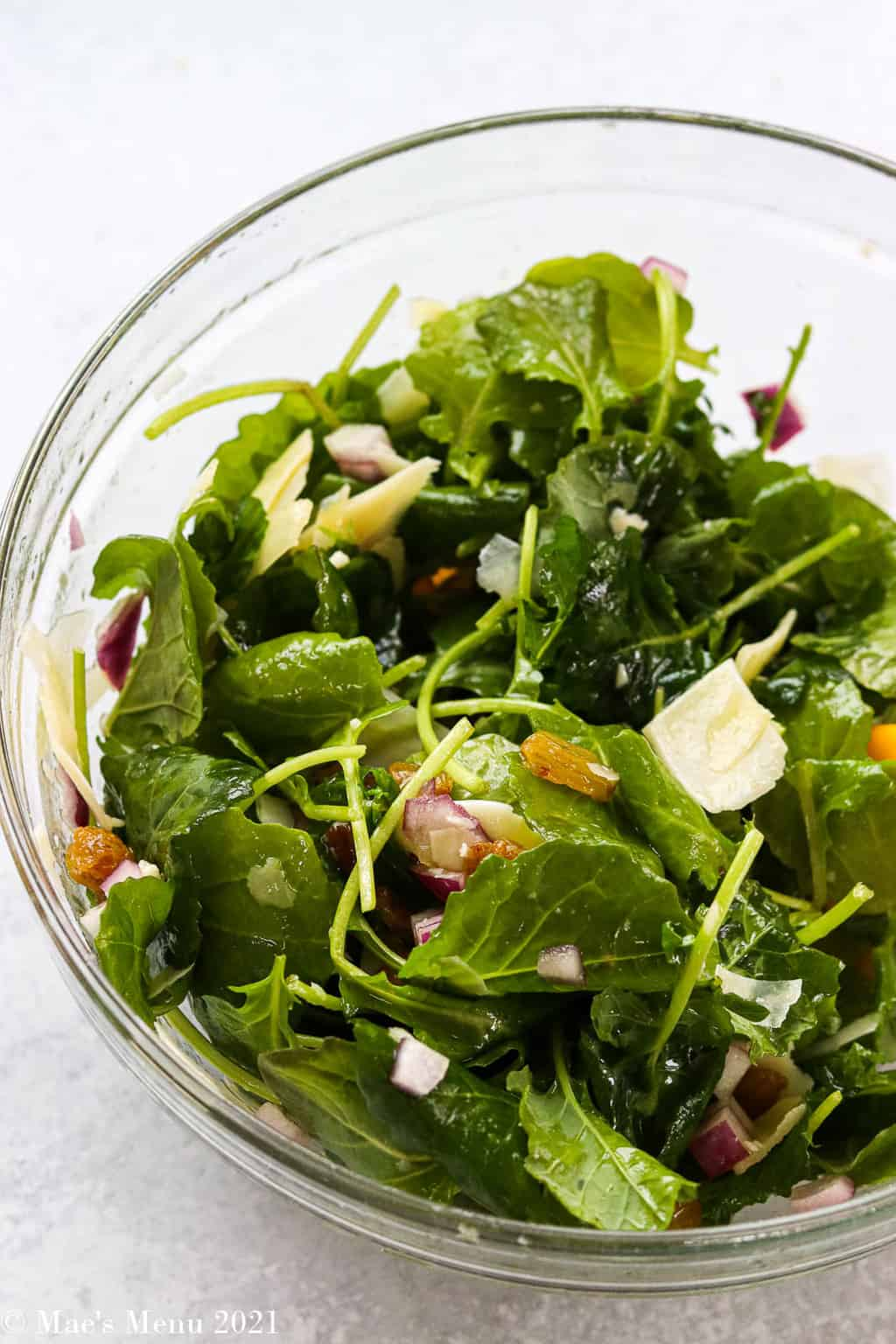 A mixing bowl with greens and cheese tossed in salad dressing