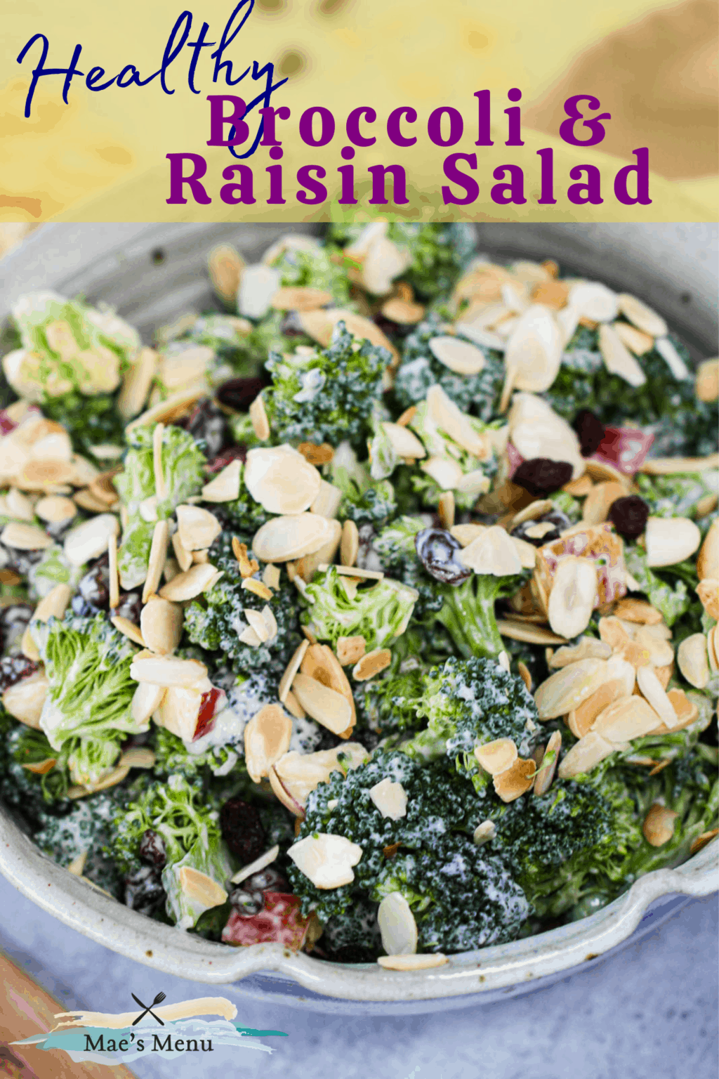 A pinterest pin for healthy broccoli raisin salad with an up-close shot of the salad in a mixing bowl