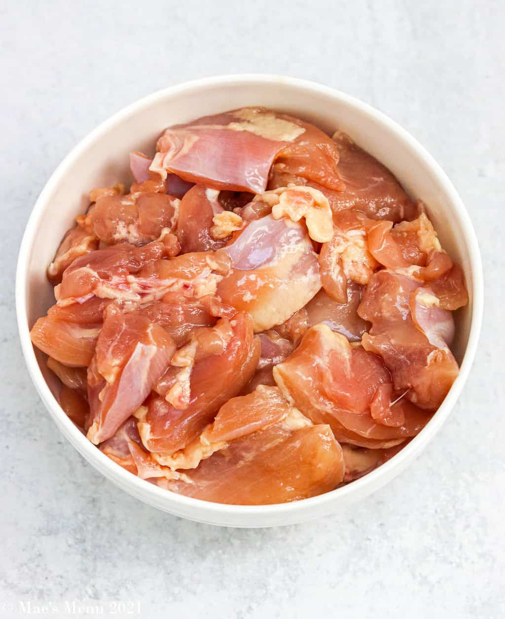 An overhead shot of a bowl of raw chicken pieces