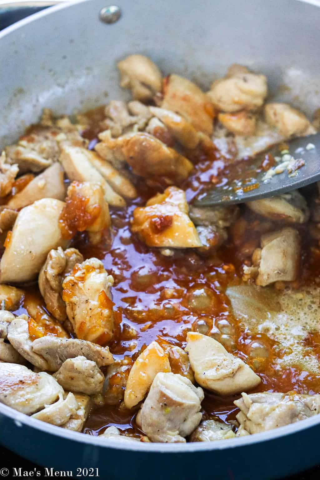Chicken and orange marmalade simmering in a saute pan