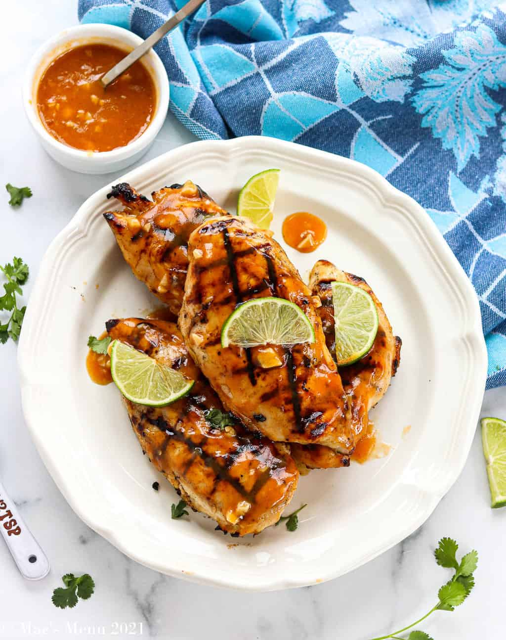 An overhead shot of a white plate full of spicy honey grilled chicken