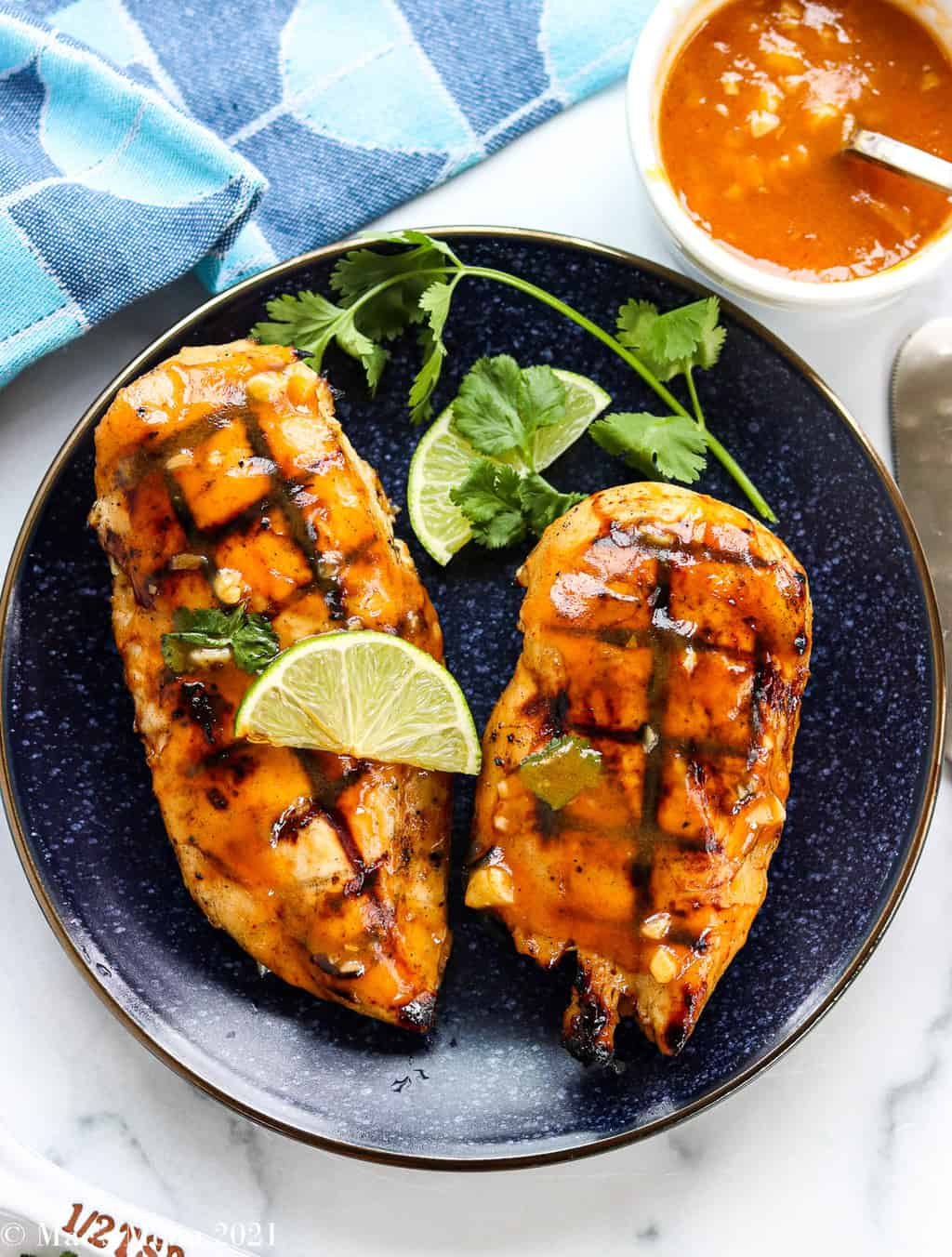 An overhead shot of a blue plate of spicy honey grilled chicken