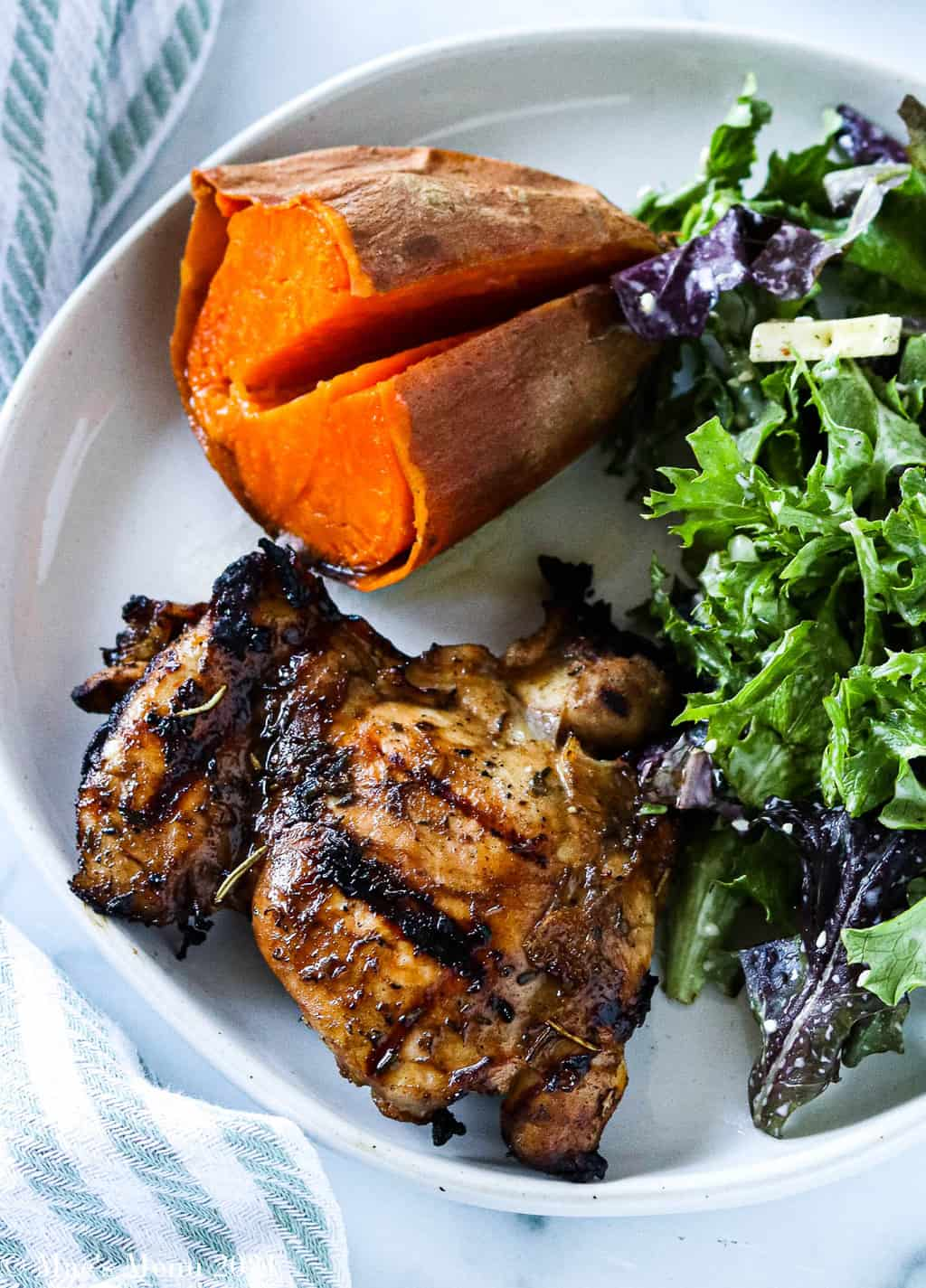 An overehad shot of a plate of the best grilled chicken thighs with a baked sweet potato and green salad