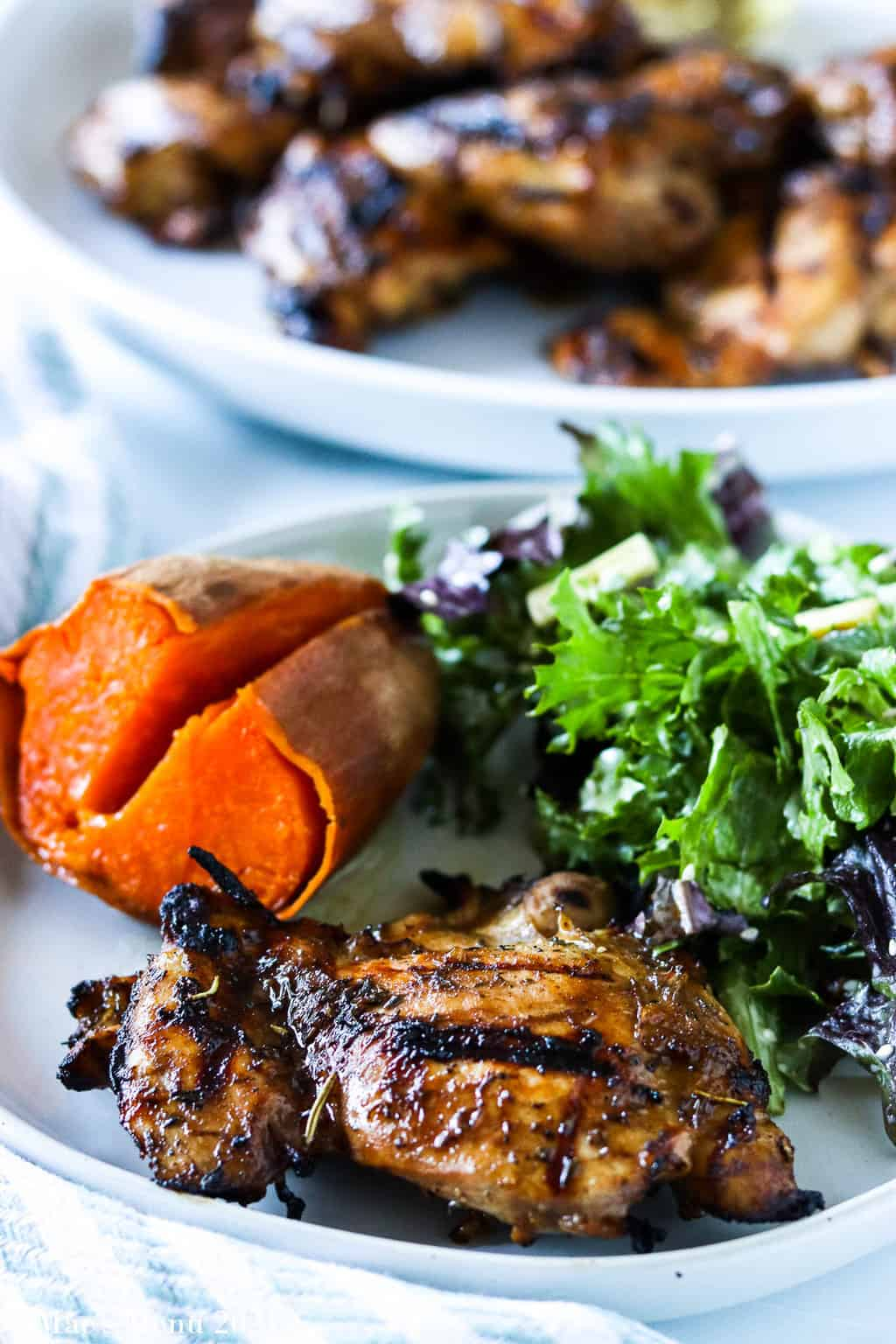 A plate of grilled chicken thighs, sweet potato, and salad