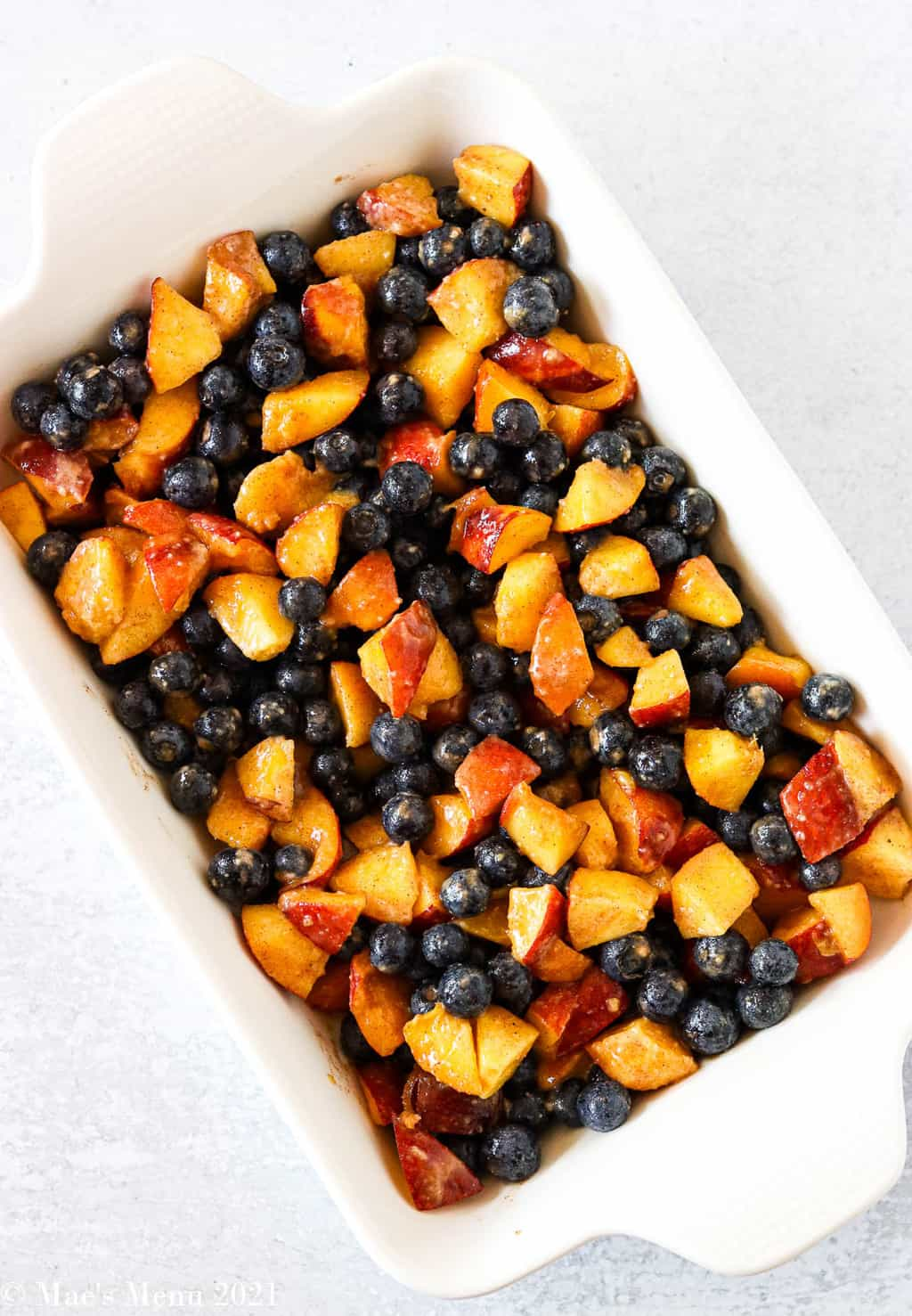 An overhead shot of a pan of blueberries and peaches in a baking dish
