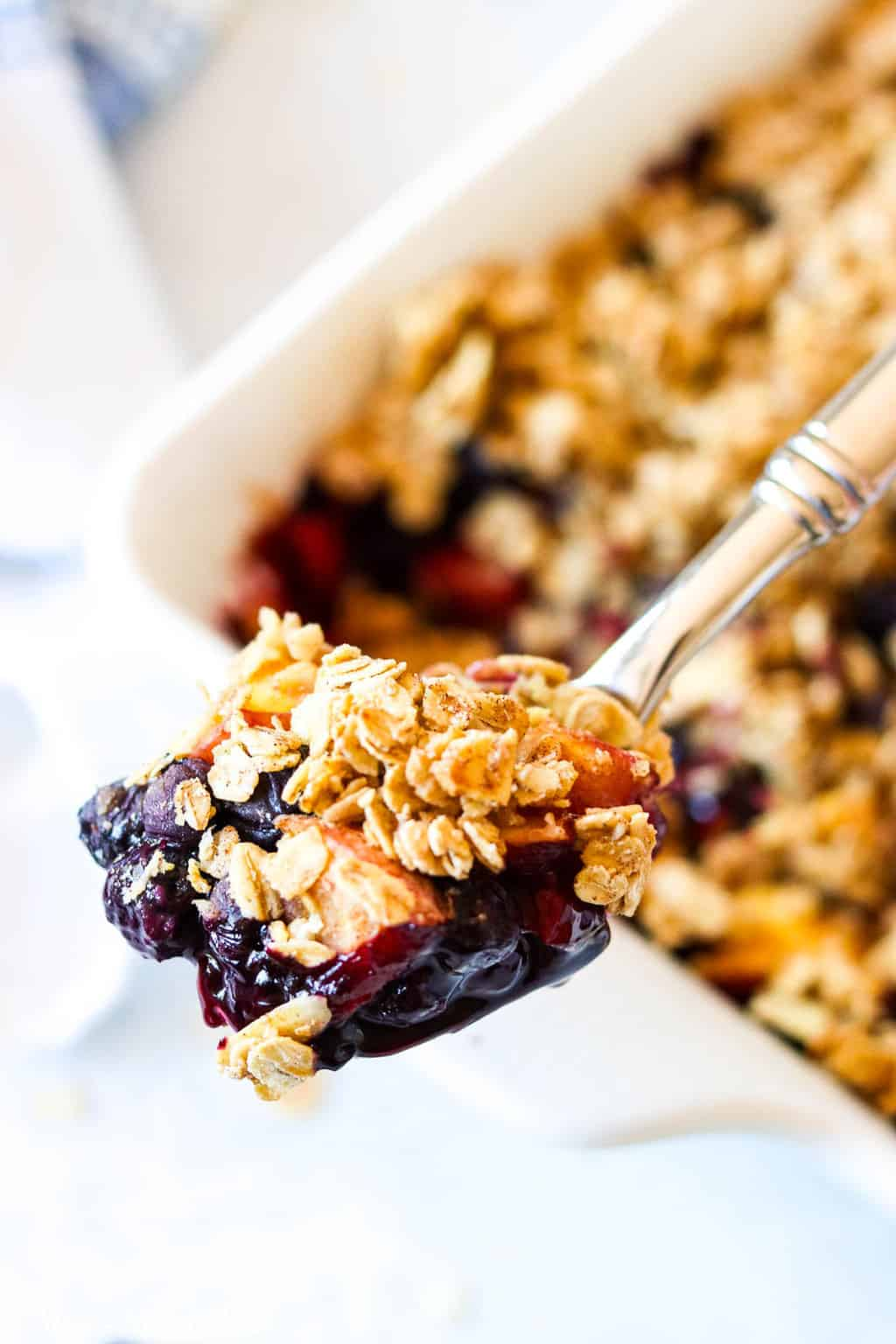 A spoonful of blueberry crisp over the baking dish