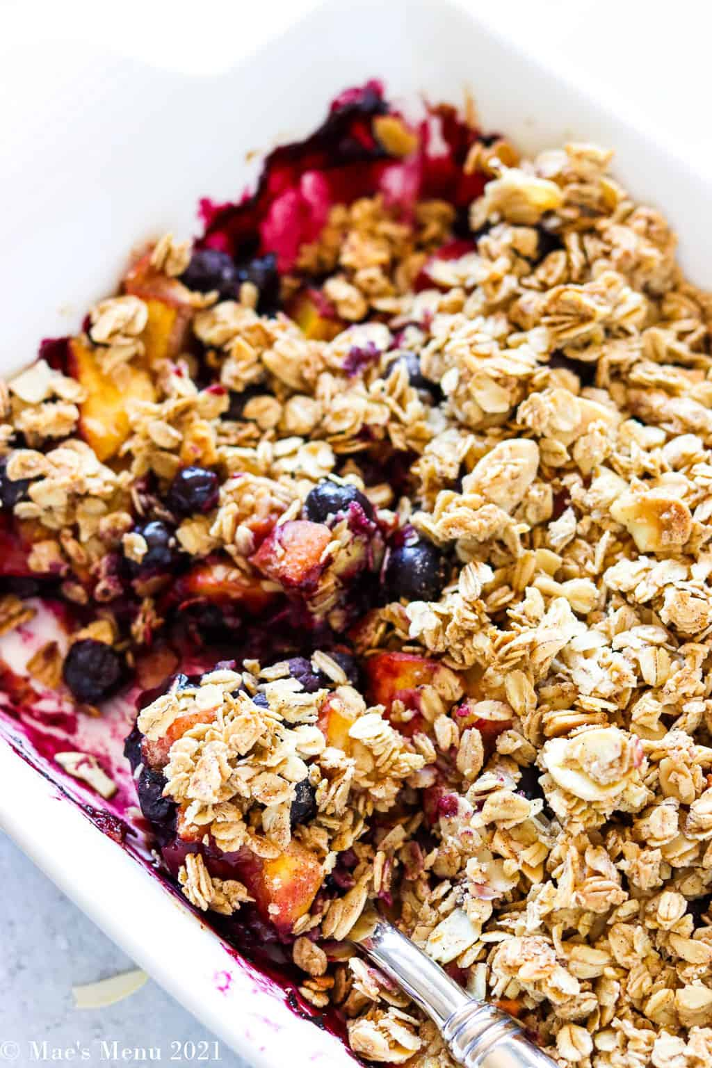 a pan of peach blueberry crisp with a spoon in it