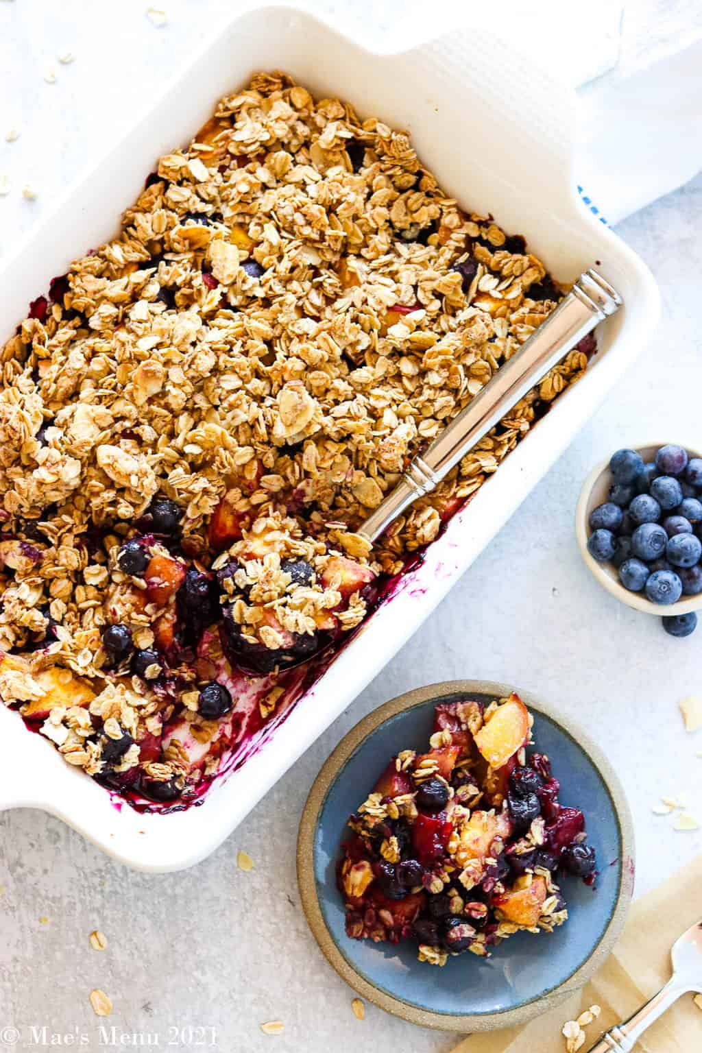 an overhead shot of a pan blueberry crisp next to a small dish of it