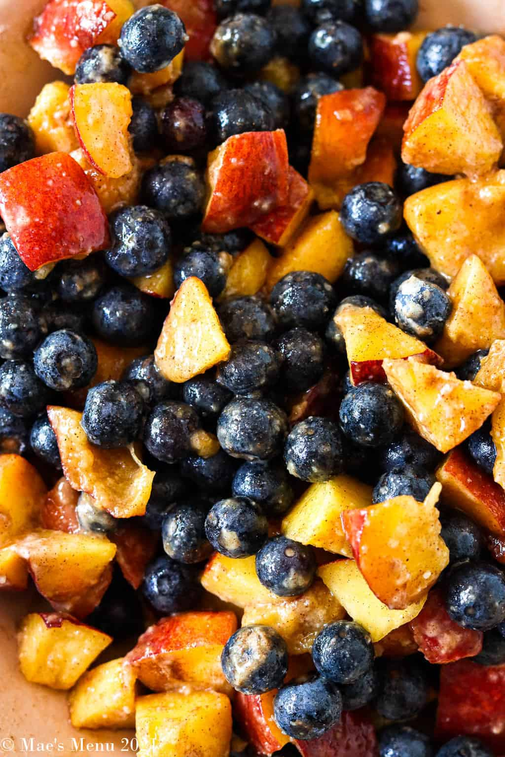 An overhead shot of blueberries and peaches mixed together with spices and sugar