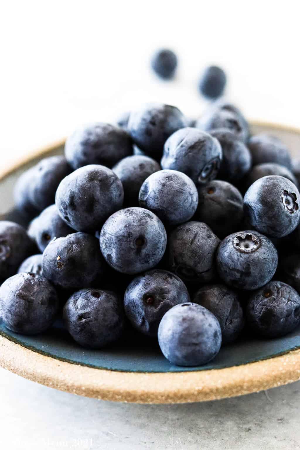 An u;-close shot of blueberries on a blue dish